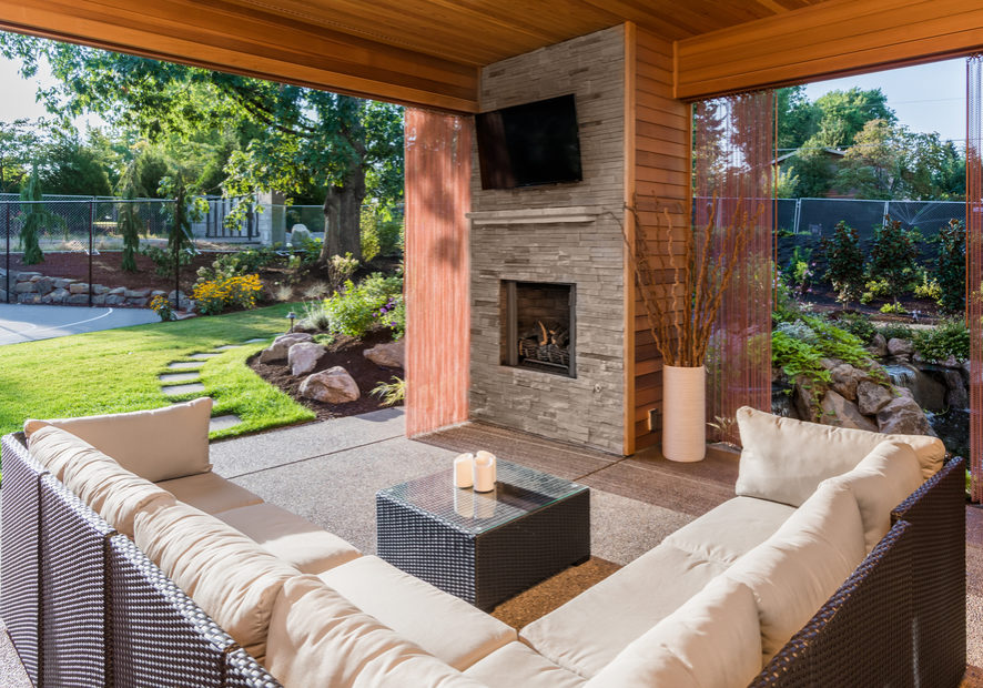 Beautiful covered patio outside new luxury home with television, fireplace, and lush green yard